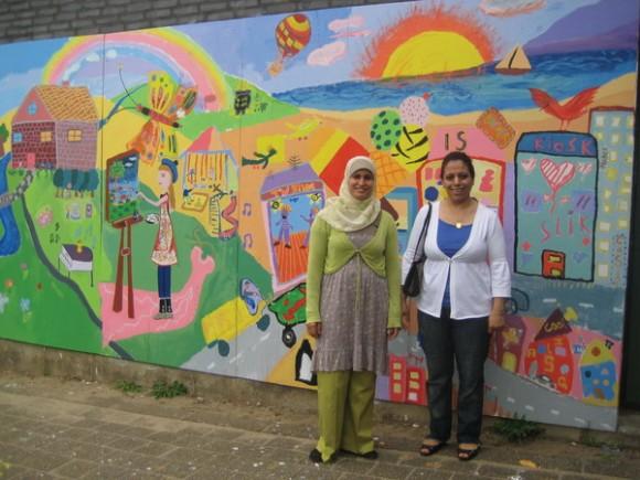 Wissal El Arid (tv) og Suhad Hamad foran det store maleri, som børn og voksne var fælles om at lave under sommerkurserne.