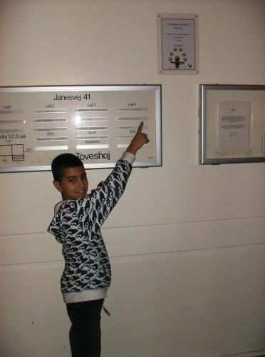 Younes på 10 år peger på vinderskiltet i opgangen på Janesvej 41