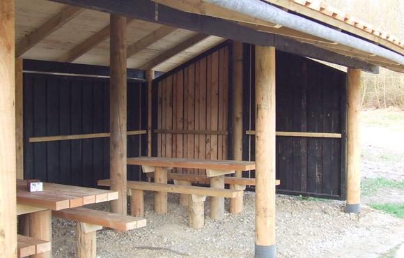 """Et kig ind i picnic-hytten på plads """"beta"""". Her har der endnu ikke været gang i grill på bordene."""
