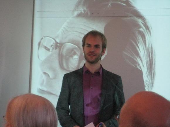 Doron Haahr byder velkommen foran billede af Knud Blach Petersen ved et tidligere arrangement