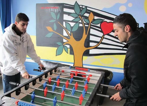 """""""Når man er sammen om gode oplevelser, lærer man hinanden at kende. Så smider man ikke sten efter hinanden,"""" siger koordinator for Unge4Unge, Wamid Hassan (th),som her spiller bordfodbold med Ahmed Hamdan."""