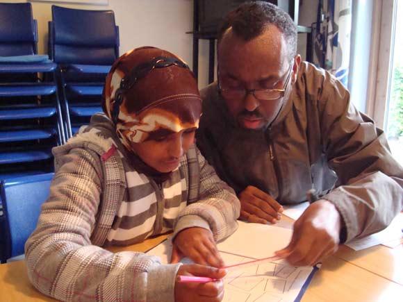 Abdirahman M. Iidle hjælper Nada, som går i 3. klasse, med sine lektier i Leg og Lærs lektiecafé i Frydenlund. Foto: AarhuSomali.