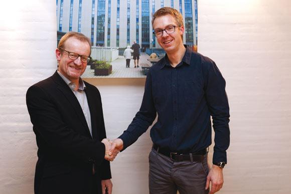 Det Boligsociale Fællessekretariats nye leder, Bertil Mahs (tv.), hilser på den afgående leder, Jens Møller, som har fået nyt job i boligforeningen Alboa.