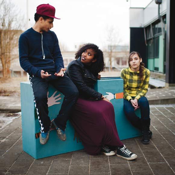 De tre unge bænkebyggere er fra venstre, Ahmed Said, Hodan Farah, og Maha Nabhan.  De viser, hvordan Gellerupbænken kan bruges til at sidde og tage en lille snak.
