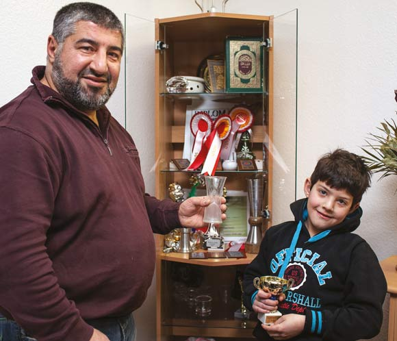 Forsiden: Mohammed og sønnen Omar foran pokalskabet, hvor  den bedste pokal er glasvasen fra 2005. Foto: Martin Krabbe