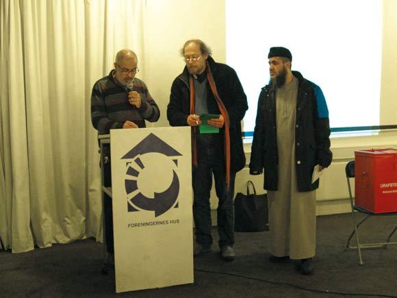 Aftenens ordstyrer, Khaled Mansour, offentliggør det første afstemningsresultat, assisteret af Peter Iversen, stemmeudvalget, og observatør Abu Bilal.