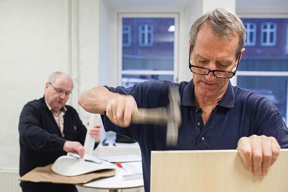 Formand Jesper Pedersen (i baggrunden) og næstformand Anders Andersen er selv med til at indrette butikken. Her samler de møbler fra IKEA.