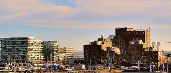 Med naboerne Lighthouse til venstre og Isbjerget i baggrunden – og Z-huset under opførelse – ligger Havnehusene mellem by og bugt.