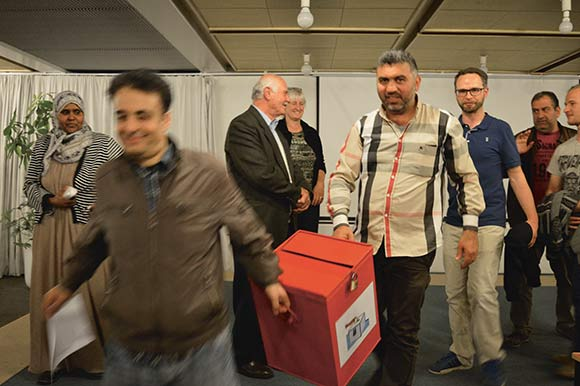 Stemmeboksen blev fyldt med næsten 1500 stemmer – en tung opgave for stemmeudvalget. Her bæres boksen af Nezar Ajjawi (tv.) og Youssef Abdul Kader.