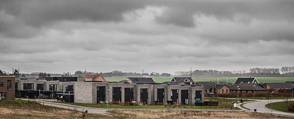 Pilevangen med sine grå-sorte boliger skyder frem i nybyggerkvarteret omgivet af åbne marker.