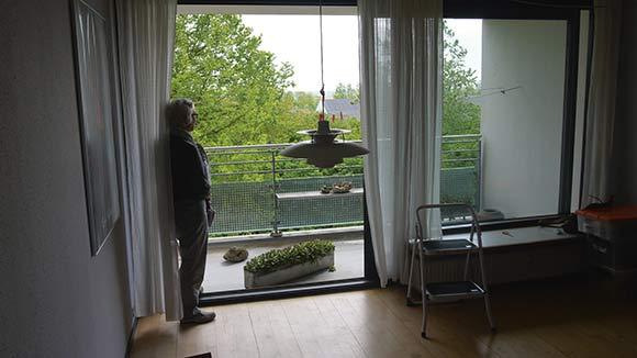 Ann Krogsager står i den tomme stue på Bentesvej og tager afsked med udsigten ned over Gellerupparken.