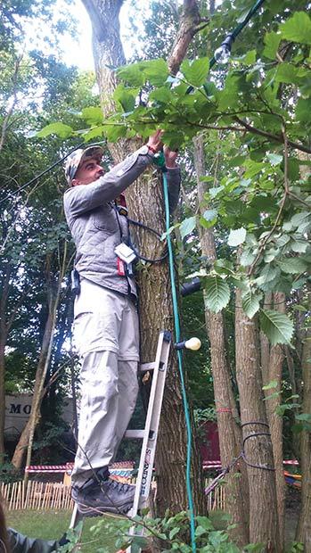 Walid hjælper med lyskæderne, der gør frivilligområdet mere hyggeligt.