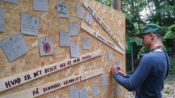 Walid er også med på at skrive på frivilligvæggen.
