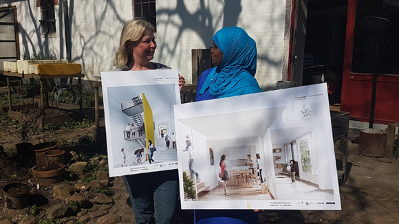 Anett og Ilham viser plancherne frem i Laden solrige have.