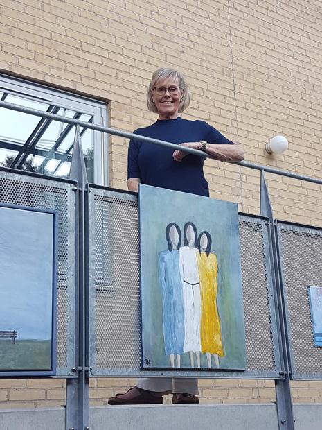 Birgitte Frølich med et af sine mange malerier.