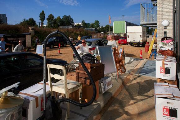 Flyttekasser og møbler stablet op på fortovet.