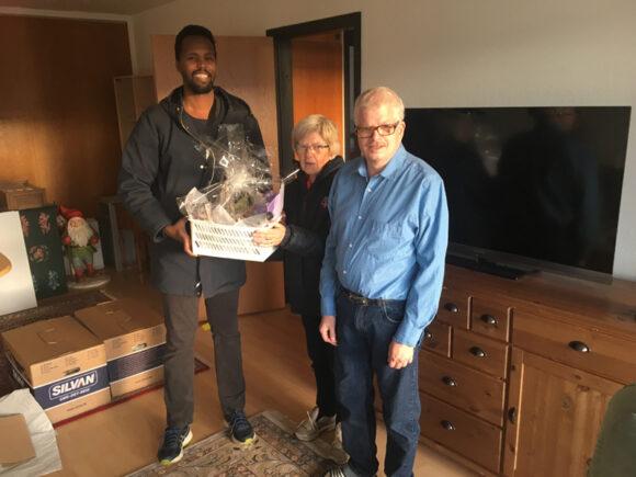 Inga Sørensen og sønnen Henrik fik overrakt en gavekurv af afdelingsformand Abdinasir Jama, fordi de har boet 50 år i Gellerupparken.