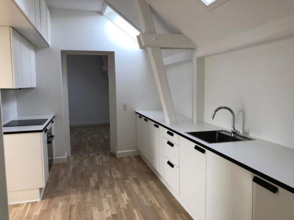 Der er hvide Svanekøkkener i alle lejligheder, og i flere af dem har man bygget skabe henover dørene for at udnytte pladsen.