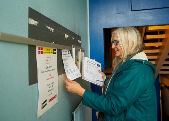 Helle Hansen hænger indbydelse til infocafé op i opgangene.