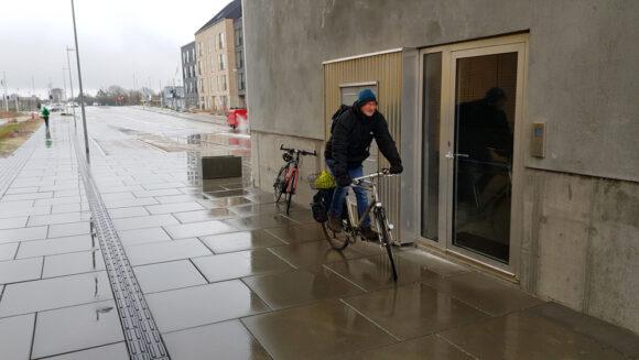 Udgangsdøren fra opgangen Gudrunsvej 44, hvor cykelstien starter og slutter lige på begge sider af porten. Kommunen har opsat to blomsterkummer, for at cyklisterne bliver nødt til at køre lidt uden om døren, hvis de ligesom cyklisten på billedet vælger ikke at stå af og trække.