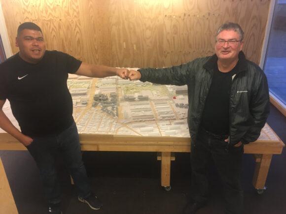 Chadi Ali Kayed (tv) banker næve med Anders Glahn hen over modellen af Gellerup og takker den kommunale tjenestekarl for hans mangeårige indsats for området.